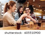 smiling young women clinking... | Shutterstock . vector #605510900