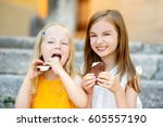 two cute little sisters eating... | Shutterstock . vector #605557190