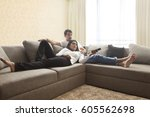smiling couple sitting on sofa... | Shutterstock . vector #605562698