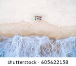 Small photo of Top view of group of happy friends lying on the beach near the stormy sea and dreaming. Aerial view two couples relax on the beach.