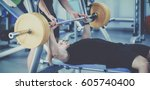 young man lifting the barbell... | Shutterstock . vector #605740400