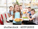 cute girl holding plate with... | Shutterstock . vector #605918303