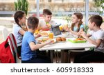 Stock photo children sitting at cafeteria table while eating lunch 605918333