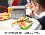 school boy eating delicious... | Shutterstock . vector #605927453