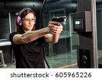 a woman firing a hand gun at an ... | Shutterstock . vector #605965226