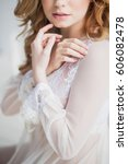 Small photo of boudoir bride's morning, a beautiful girl with crossed arms ajar lips close-up in a white lace transparent dress
