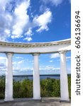 Small photo of White doric columns against bushes river and blue sky with clouds