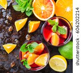 Small photo of Traditional cold spanish sangria cocktail with red wine and ingredients on a black table, citrus fruit orange lime lemon mint leaves and ice for hot summer days. Top view flat lay overhead