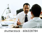 Small photo of Two businessmen in office having a discussion