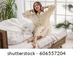 serene woman sitting on soft bed | Shutterstock . vector #606557204