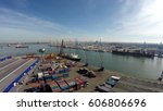 Small photo of Aerial flight above harbor flying over container terminal cranes and ship showing in background with helicopter pad and furthermore water and industrial landscape zone blue sky background 4k quality