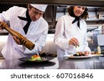 two chefs garnishing meal on... | Shutterstock . vector #607016846