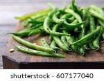 green beans on wooden cutting... | Shutterstock . vector #607177040
