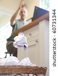 A frustrated man throwing a crumpled piece of paper into an overflowing wastebasket - stock photo
