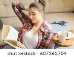 young woman reads book at home... | Shutterstock . vector #607362704