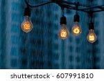 Rainy day at the modern city street. Light bulbs garland against urban buildings background. - stock photo