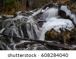 Small photo of White flowy water cascading over a waterfall with a natural ice sculpture in the falls