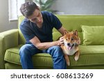 Stock photo young hansome male in blue t shirt having fun with his lovely shiba inu dog snuggling stroking 608613269