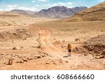 Small photo of Backpacker tourist man back view walking hiking stone desert trail dirt road towards mountains, Ramon crater traveling journey, Israel journey landscape nature.