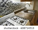 Stock photo a clean and bright small kitchen in an apartment with concrete countertop and tile backsplash 608714513