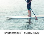 man standing on paddleboard in... | Shutterstock . vector #608827829