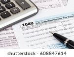 tax form with pen and calculator | Shutterstock . vector #608847614