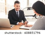 Visiting car dealership. Handsome sales manager is smiling while beautiful client is signing papers - stock photo