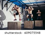 Small photo of Fit young people doing box jumps as a group in a gym