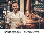 handsome bartender in apron is...   Shutterstock . vector #609098996