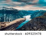 Stock photo a man sits while throwing his arms in the air on the mountain s cliff edge of trolltunga throning 609325478