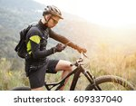 Small photo of People, sports, active lifestyle and modern technology. Outdoor picture of cyclist on booster bike using navigator on smart phone, exploring map and searching GPS coordinates while biking in mountains