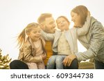 cheerful family hugging outdoor. | Shutterstock . vector #609344738