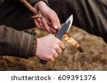 Close-up hand hunter man with knife cut a wooden stick for campfire in the forest.  Bushcraft, hunting and people concept - stock photo