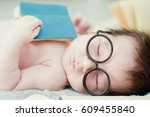 baby boy in glasses with books | Shutterstock . vector #609455840