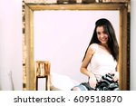Small photo of Chic young woman admires herself in the mirror