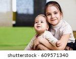 elder sister hugging with her... | Shutterstock . vector #609571340