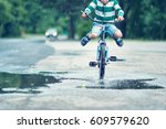 child on a bicycle at asphalt... | Shutterstock . vector #609579620