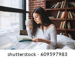 woman reading book with cup of...   Shutterstock . vector #609597983