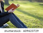 woman with a book in spring park | Shutterstock . vector #609623729