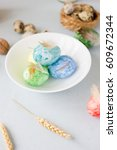 Small photo of Green, yellow and blue easter eggs on ceramic bowl, bright and airy shot