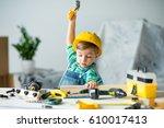 cute little boy in yellow hard... | Shutterstock . vector #610017413