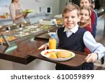 Stock photo cute girl holding tray with delicious food in school cafeteria 610059899