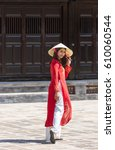 Small photo of a woman in red ao dai Vietnamese's traditional costumes walking in the ancient city