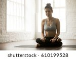 Small photo of Young attractive yogi woman practicing yoga concept, sitting in Agni stambhasana exercise, Fire Log, Ankle to Knee pose, working out, wearing sportswear, full length, white loft studio background