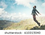 happy man jumping at mountains... | Shutterstock . vector #610315040