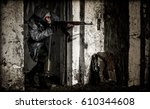 Small photo of Man in gas mask, grey coat, camouflage pants and rifle takes aim peering over a wall inside a destroyed building. Nuclear post apocalypse world war concept.