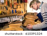 luthier looking inside the body ... | Shutterstock . vector #610391324