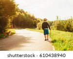 Stock photo boy and dog walk on contryside road at the evening summertime 610438940