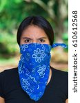 Small photo of Young brunette woman wearing blue bandana covering half of face, interacting outdoors for camera, activist protest concept.