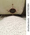 Small photo of White alumina balls on the floor after pouring from ball mill machine.